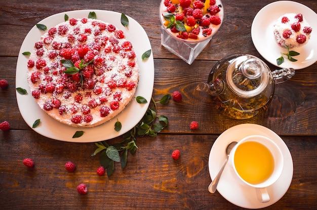 Sobremesas vegetarianas de framboesa com chá de ervas na mesa de madeira