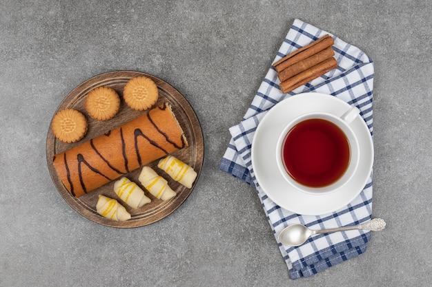 Sobremesas, xícara de chá e canela em pau na superfície de mármore