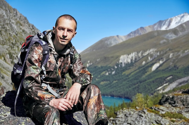 Sobrevivência na natureza. um homem camuflado descansando entre as montanhas. perseguidor, sobreviver