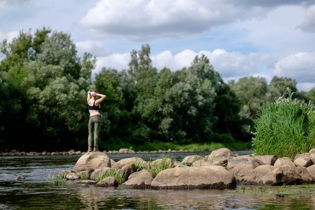 Sobreviver e viajar conceito. mulher branca magra, vestida com roupa militar, de pé na margem rochosa do rio.