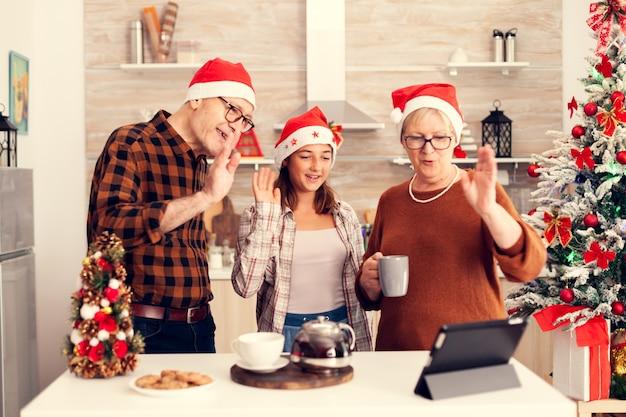 Sobrinha e avô comemorando o natal dizendo olá durante uma ligação online