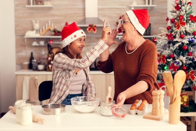 Sobrinha e avó no dia de natal gostando de fazer bolos