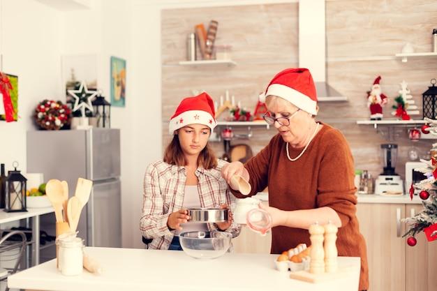 Sobrinha no dia de natal fazendo biscoitos com a avó