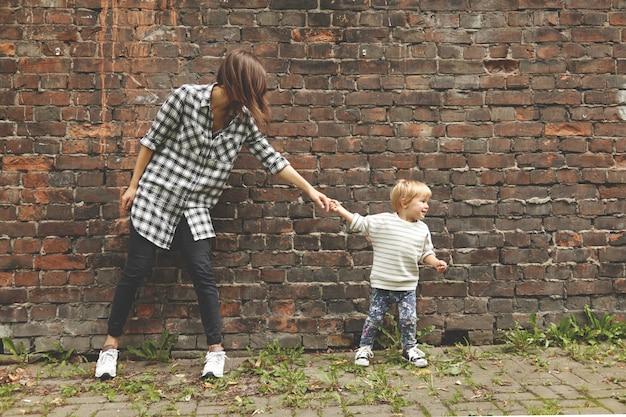Sobrinho puxando sua tia mais velha para ir mais longe. jovem de camisa xadrez, calça preta em pé no lugar perto da parede de tijolos. garoto minúsculo em jeans e suéter despojado quer que sua tia o siga.