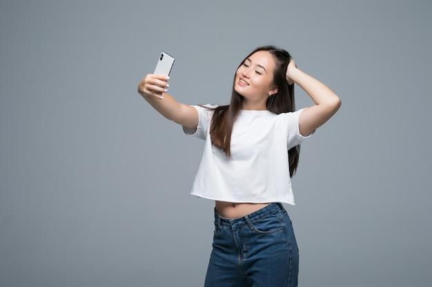 Sociável menina asiática linda tomando selfie ou falando na vídeo chamada usando telefone celular sobre fundo cinza