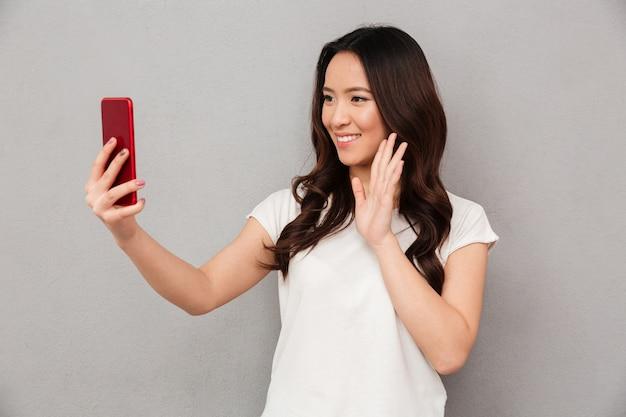 Sociável mulher bonita com aparência asiática tomando selfie ou falando na chamada de vídeo usando o telefone celular, isolado sobre a parede cinza