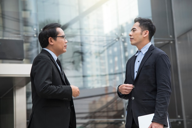 Sócio asiático do homem de negócios que consulta e que discute para o negócio