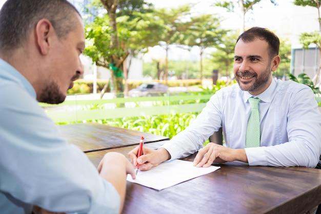 Sócios de negócio bem sucedidos alegres que discutem o contrato