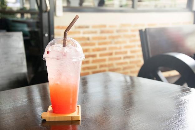 Soda congelada da morango com palha no copo plástico na tabela.