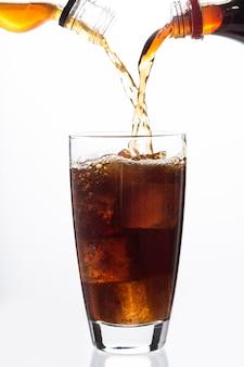 Soda e álcool enchendo um copo com cubo de gelo