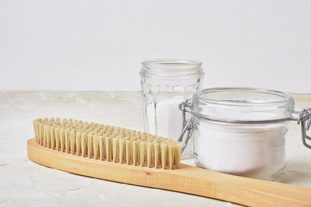 Soda escova de madeira em potes sobre um conceito de limpeza ecológica de fundo claro