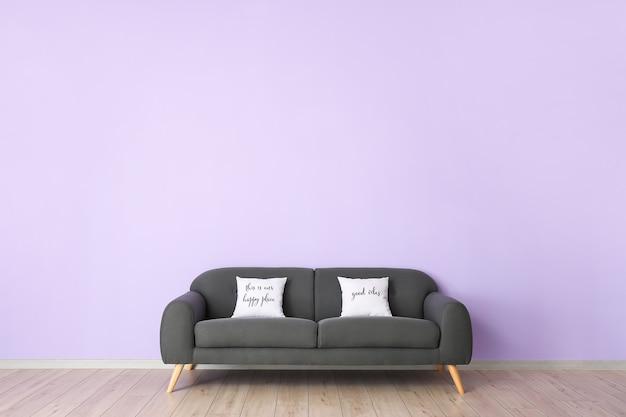 Sofá aconchegante com almofadas perto da parede colorida do quarto