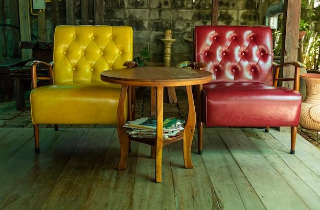 Sofá amarelo e sofá vermelho no chão de madeira no terraço.
