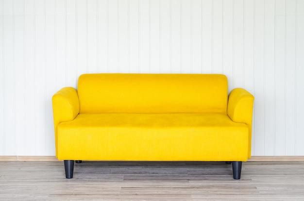 Sofá amarelo no fundo da parede branca