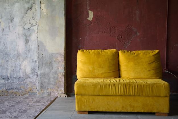 Sofá amarelo sobre a parede de tijolo vermelho em um estúdio de estilo loft