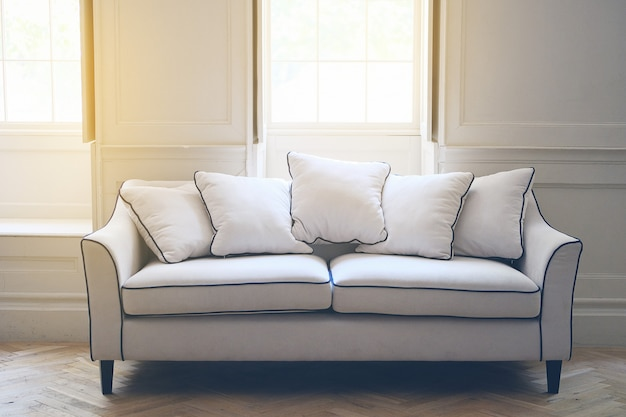 Sofá branco no interior no estilo inglês. a luz solar entra pelo windows.