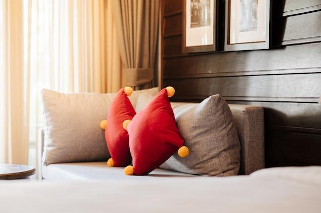 Sofá cinza com almofadas vermelhas