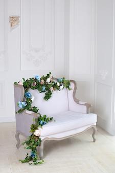 Sofá clássico de têxteis leves em uma sala vintage. um interior real clássico claro com um sofá macio com estofamento em tecido. interior elegante luxo real com paredes brancas e sofá cinza. relaxamento