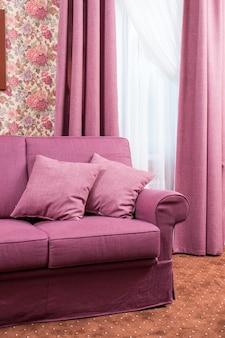 Sofá com duas almofadas em um sofá perto da janela