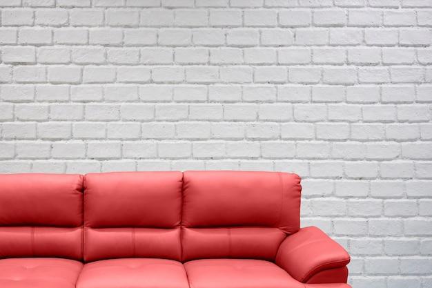 Sofá com parede de tijolo branco com copyspace em branco