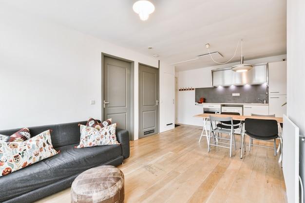 Sofá confortável com almofadas e pufe localizado perto das portas e da área de jantar em um apartamento contemporâneo