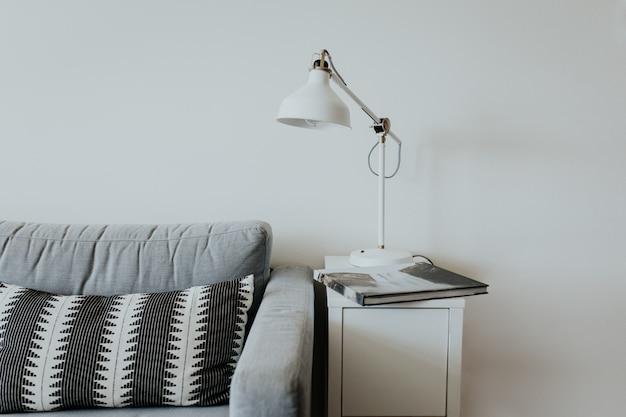 Sofá confortável em uma casa moderna com uma lâmpada em uma pequena prateleira branca e um livro com uma cachoeira