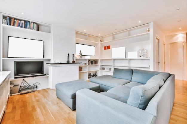 Sofá confortável localizado perto de estantes com tv e decorações na sala de estar iluminada em apartamento moderno