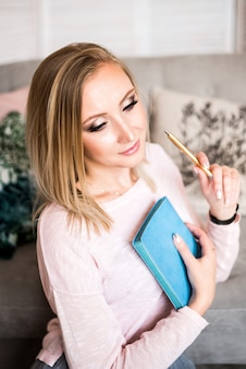 Sofá de cabelo loiro cinza de mulher, sentado com o bloco de notas e caneta, planejando em farol moderno.