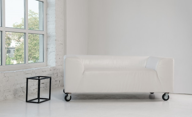 Sofá de couro branco na sala branca brilhante