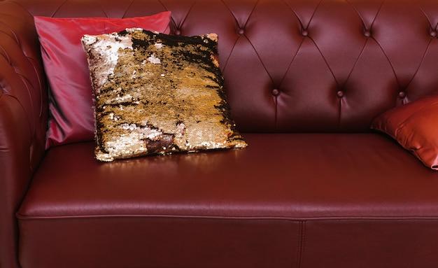 Sofá de couro com almofadas brilhantes. parede acolchoada do sofá. luxo no interior. decoração do quarto para o feriado. preparando-se para o ano novo e o natal.