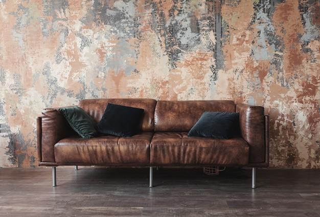 Sofá de couro com almofadas no interior do loft