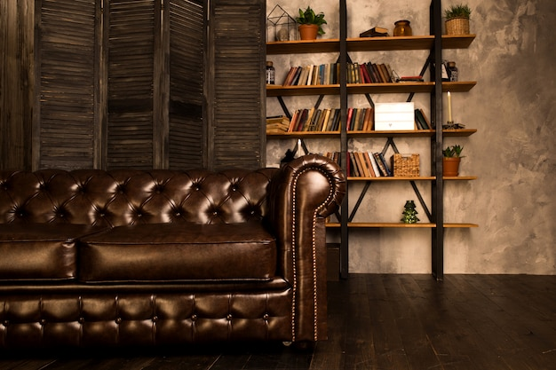 Sofá de couro marrom em uma sala interior com uma estante.