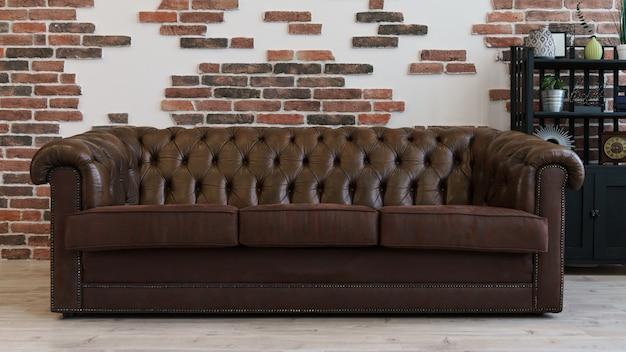Sofá de couro marrom na sala de estilo loft e parede de tijolo