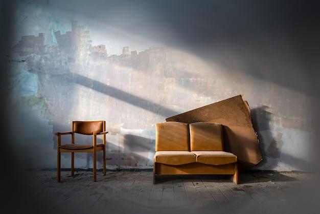 Sofá de couro velho no lado do prédio da fábrica abandonada, iluminado pelo sol. móveis rústicos em casa mal-assombrada