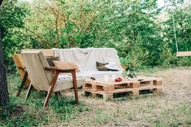 Sofá de madeira com poltrona e mesa ao ar livre do quintal. ninguém