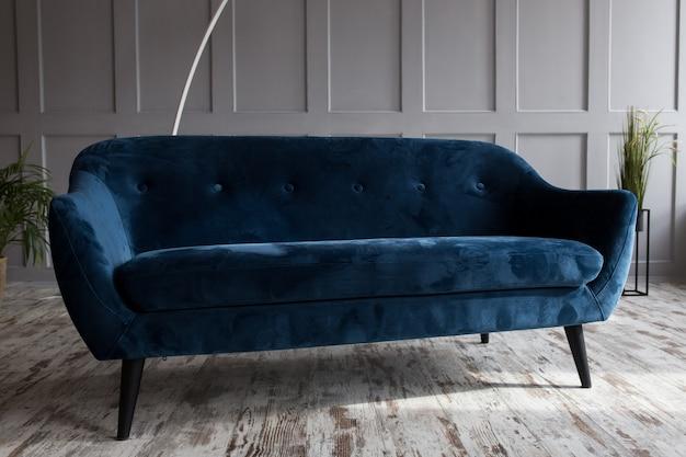 Sofá de veludo de algodão em um interior moderno do sotão no azul.