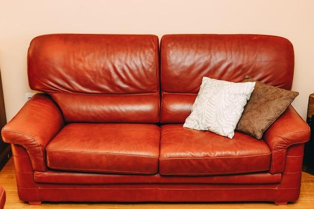 Sofá dobrável feito de couro genuíno bordô com almofadas brancas e marrons no quarto