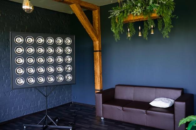 Sofá e lâmpada no moderno quarto escuro minimalista com parede de tijolo