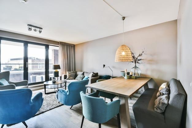 Sofá e poltronas colocados ao redor da mesa com decorações na área de jantar da elegante sala de estar em um apartamento moderno