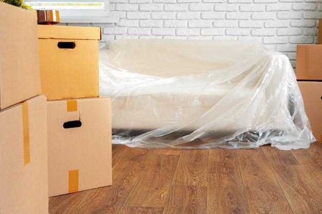 Sofá embalado e pilha de caixas de papelão em uma sala, conceito em movimento