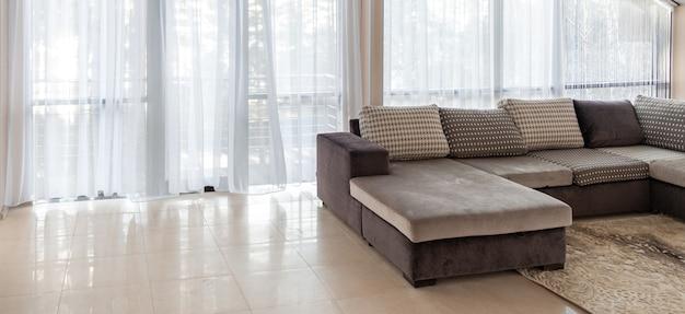 Sofá grande e grandes janelas com design de interiores com a luz do sol matinal vinda de fora