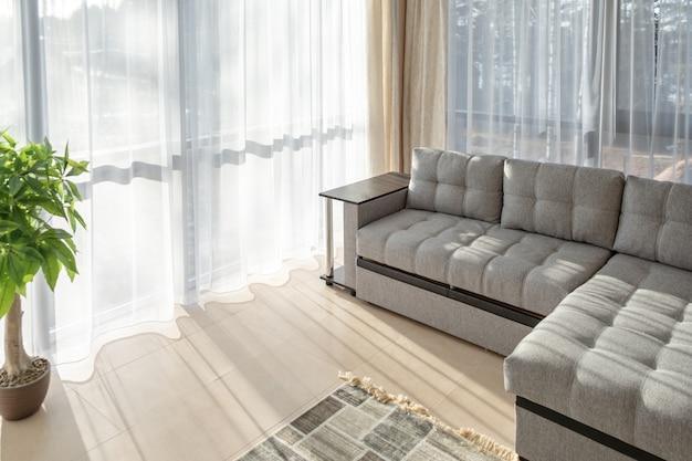 Sofá grande e janelas grandes. luz do sol da manhã a partir das janelas