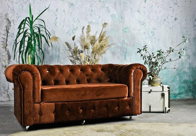 Sofá laranja vintage contra uma parede rústica. interior rústico