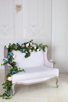 Sofá leve em uma sala vintage. interior real clássico com um sofá macio com um estofamento em tecido. interior elegante luxo real com paredes brancas e sofá cinza.