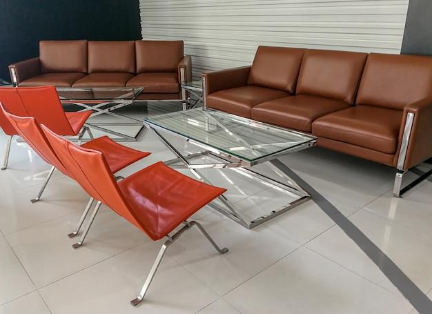 Sofá marrom vazio e tabela de vidro e cadeira alaranjada na sala de visitas no escritório para negócios, conceito interior do escritório, conceito de espera.