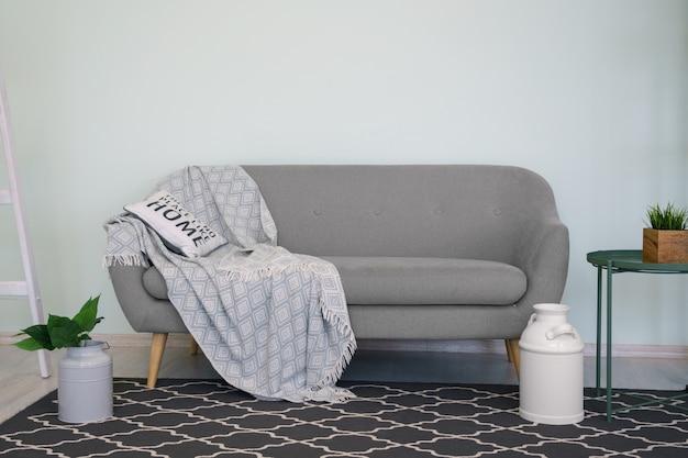 Sofá moderno cinza com almofada e cobertor e tapete preto