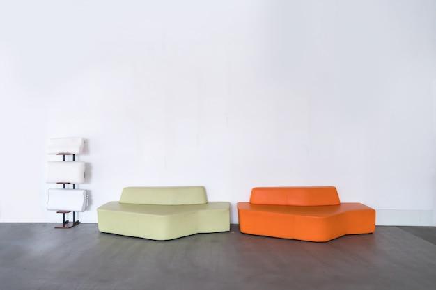 Sofá moderno laranja e verde na sala vazia