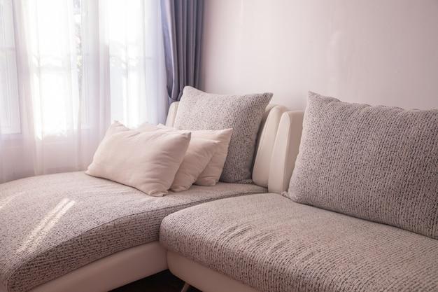 Sofá moderno na sala de visitas com luz solar morining no fundo das janelas da cortina.