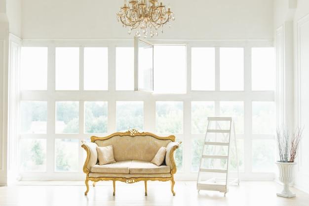 Sofá retrô clássico com inserções de ouro fica no fundo da janela, design de interiores