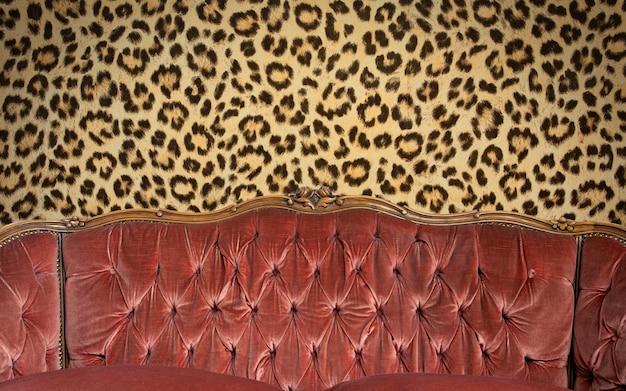 Sofá rosa elegante e moderno com ponto de transporte, botões e parede de padrão leopardo, espaço de design moderno para texto, detalhes de espaço de cópia